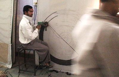 Sandeep at work on a rug at the factory: Photo courtesy the artists.